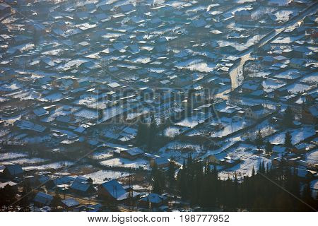 View of the city of Ust-Kut an area of private housing in November. Eastern Siberia Irkutsk region houses yards vegetable gardens view from the hill