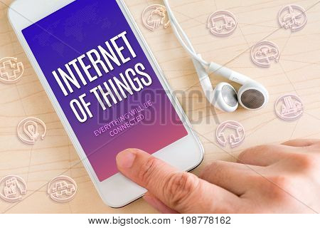 Hand Touch Smart Phone And Ear Phone With Internet Of Things (iot) Word On Wood Table ,digital Techn