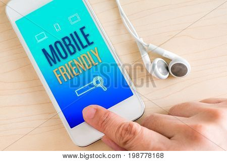 Hand Touch Smart Phone And Ear Phone With Mobile Friendly Word On Wood Table,digital Lifestyle Conce