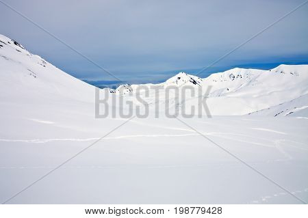 Mountain range after a snowfall and the trails of bear spring in Kamchatka. Bear hunting in may in far East Russia