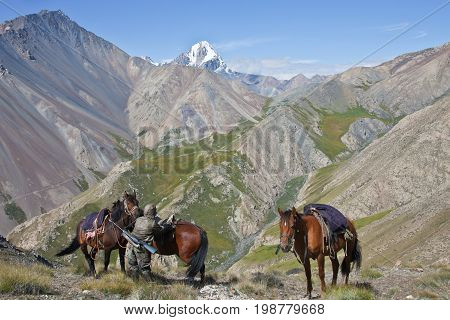 Hunter with rifle in the mountains of Tien Shan ties the three horses on the background peaks scree and rocks. Kyrgyzstan