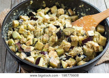 Cubes of eggplant in a frying pan on the table