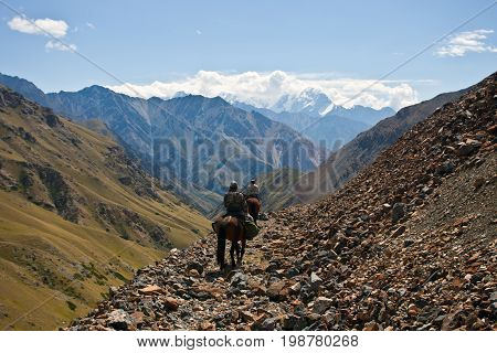 Two hunters on horseback riding in the mountains of Tien Shan Kyrgyzstan. Steep slopes cliffs rock slides in inaccessible mountains.