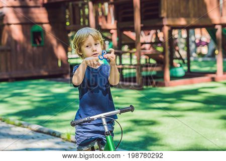Boy Playing With Fidget Spinner. Child Spinning Spinner On The Playground. Blurred Background