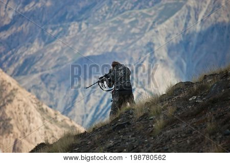 Hunter in camouflage looks into the optical sight of a rifle in the mountains of Tien Shan Kyrgyzstan