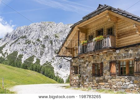 Old stone hut with mountain Gartnerkofel in the background on Nassfeld in Carnic Alps in Austria