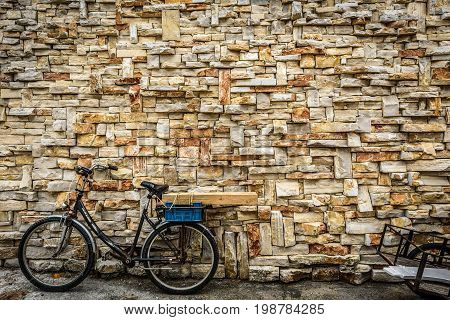 Old rusty vintage bicycle bike and decorative stone wall. Street photo of old bike and trolley leaned against a stone wall on a street of Silba Croatia.