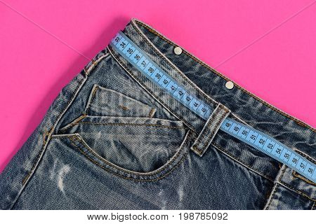 Top part of denim trousers isolated on pink background. Healthy lifestyle and dieting concept. Close up of jeans belt loops and pocket. Jeans with blue measure tape instead of belt.