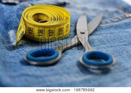 Scissors And Yellow Measure Tape On Jeans As Design Concept