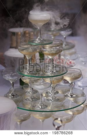 Pyramid of champagne glasses with liquid nitrogen. Champagne glasses with sparkling wine in the pyramid