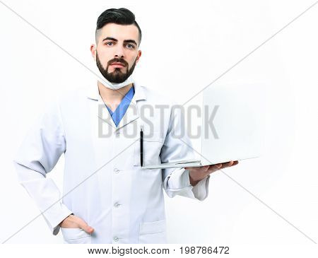 Guy in surgical mask isolated on white background. Treatment and medical technologies concept. Doctor with beard holds white laptop. Man with confident face expression in white hospital uniform