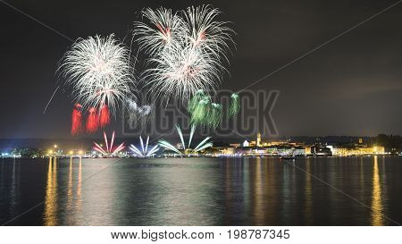 Fireworks on the lakefront of Arona over the Maggiore Lake in a summer evening with sky and clouds in the background