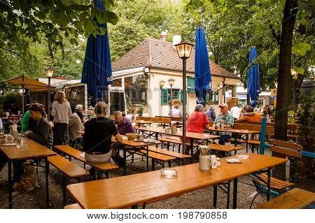 MunichGermany-August 072017: People relax at noon while eating in a local biergarten under its trees.