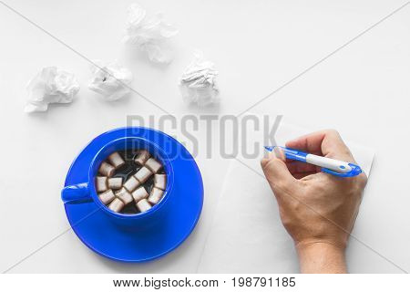 Cup of coffee on saucer with marshmallows hand with pen writing on a blank sheet of paper on the wooden white background and crumpled sheets of paper. Business plan. Writing poetry. Never give up.