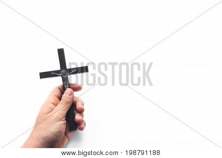 Closeup of wooden christian cross in the hand on the white isolated background. Church utensils. Man holding a crucifix.