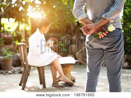 Romantic concept with man holding white rose and ring making marriage proposal