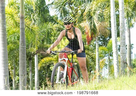Road bicycle women mountainbiker riding downhill in forest