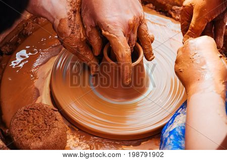 Dirty Hands In The Clay And The Potter's Wheel With The Product. Father Is Teaching His Daughter To