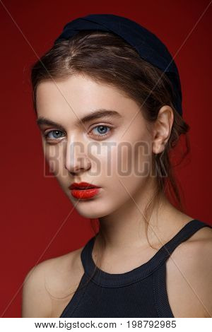 Beauty portrait of young girl with fashion make-up and brunette hair over red background. Studio portrait