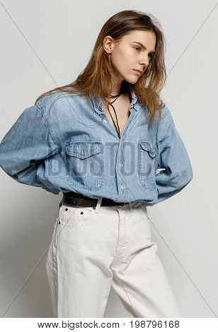portrait of happy young woman posing in jean shirt and white jeans on against white background
