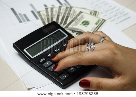 Accountant counts money with a blach calculator