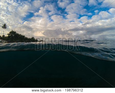 Double landscape with sea and sky. Above and below waterline in tropical seashore. Dark seawater and sunny sky. Sunset on beach. Exotic island shore view. Marine background. Tropical seaside swimming
