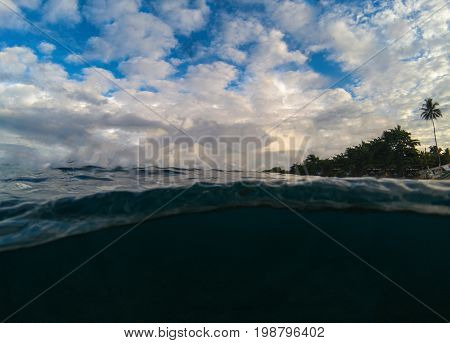 Double landscape with sea and sky. Above and below waterline in tropical seashore. Dark seawater and sunny sky. Sunset on beach. Exotic island shore view. Marine background. Tropical seaside sunset