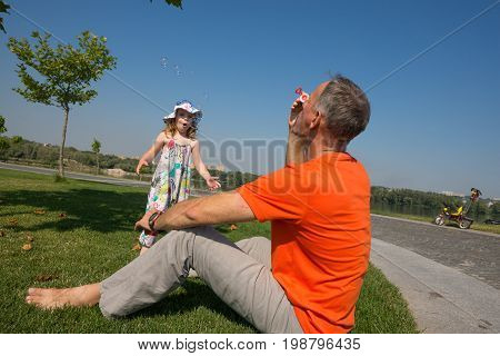 Happy Father And His Little Surprised Daughter Blowing Soap Bubbles