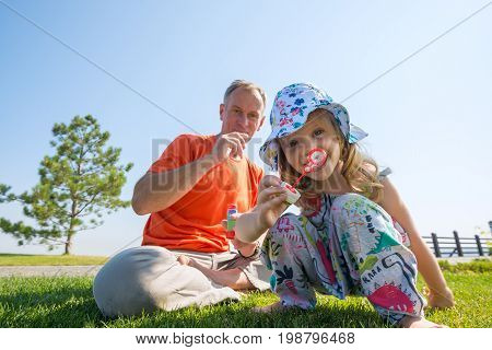Smiling Little Girl And Her Father Are Blowing Soap Bubbles