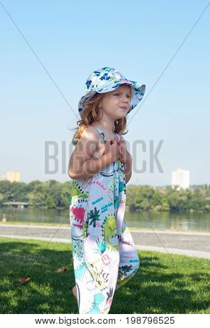 Worried Little Girl In A Hat Is Playing On The Green Lawn