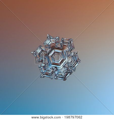 Real snowflake macro photo: smll star plate snow crystal with six short, broad arms, relief central hexagon and glossy surface. Snowflake glittering on smooth brown - blue gradient background.