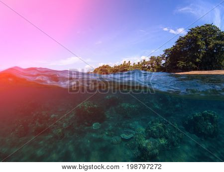Double landscape with sea and sky. Sea panorama split photo. Undersea view of coral reef. Tropical island seashore. Above and below sea waterline. Pink flare on seawater. Exotic island seaside travel