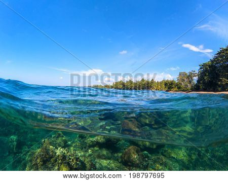 Double landscape with sea and sky. Sea panorama split photo. Undersea view with tropical island seashore. Above and below sea waterline. Snorkeling in tropical sea. Exotic island seaside vacation