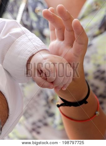 Baby Hand Gently Holding Adult's Finger