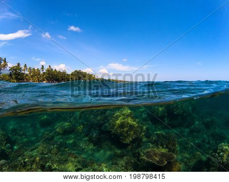Split landscape with sea and sky. Split photo with tropical island and coral reef. Clear blue sky and underwater view. Above and below sea waterline. Exotic seashore panorama. Beautiful split seascape