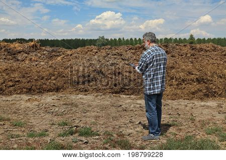 Farmer And Heap Of Dung In Field