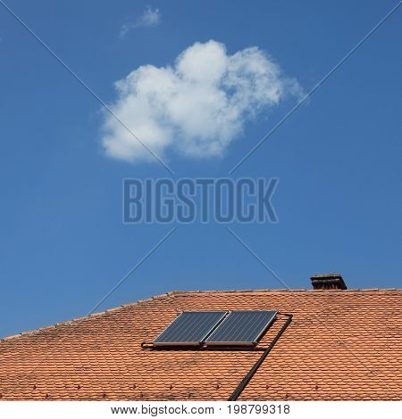 Solar panels at red tiles roof of old house for water heating with blue sky and white cloud