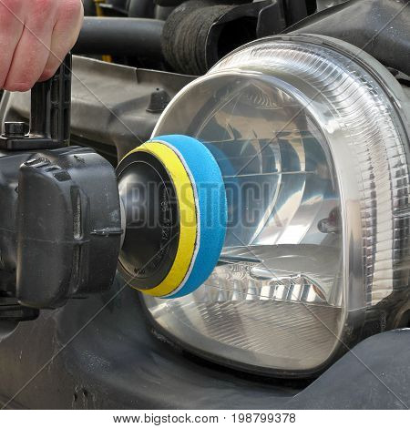 Repairing of modern car headlight closeup of light worker hand and tool