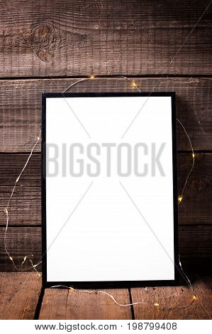 Empty black frame with twinkle light on aged wooden background. Place for text. Mock-up for design.