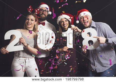 Two beautiful young couples having fun at New Year's Eve Party holding cardboard numbers 2018