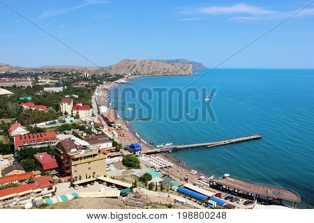 The beach town of Sudak in Crimea the view from the top of the mountain on a Sunny day. Summer the Black sea coastline. Landscape.