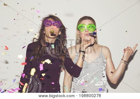 Two girl friends having fun dancing and making crazy faces while taking photos at a party