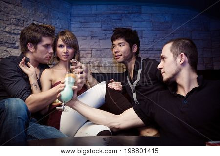 a pretty young woman is surrounded by three men trying to seduce her.