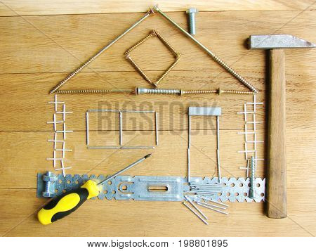 House of screws and bolts with a hammer. The concept of a modern renovation.