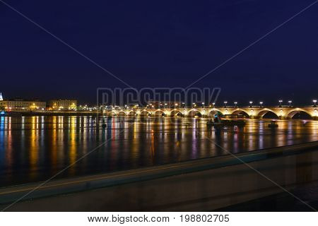 The beautiful Pont de pierre or Stone Bridge connecting the left and right banks of the Garonne River in twilight Bordeaux France