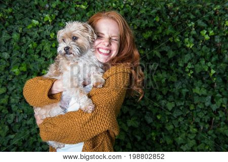 Beautiful red-haired woman has her dog on her arm