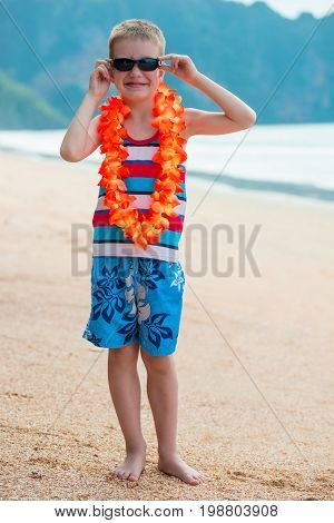 Vertical Portrait Of A Boy In Floral Lei On A Hawaiian Beach