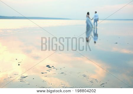Couple of lovers embracing standing barefoot in shallow water in sunset with bodies reflected