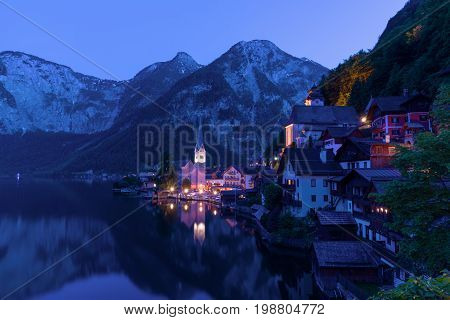Classic postcard view of famous Hallstatt lakeside town in the Alps on a dusk in the summer, Salzkammergut region, Austria