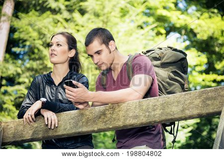 young couple hiking through the forest. the tech-addicted guy is checking his emails rather than enjoying nature.